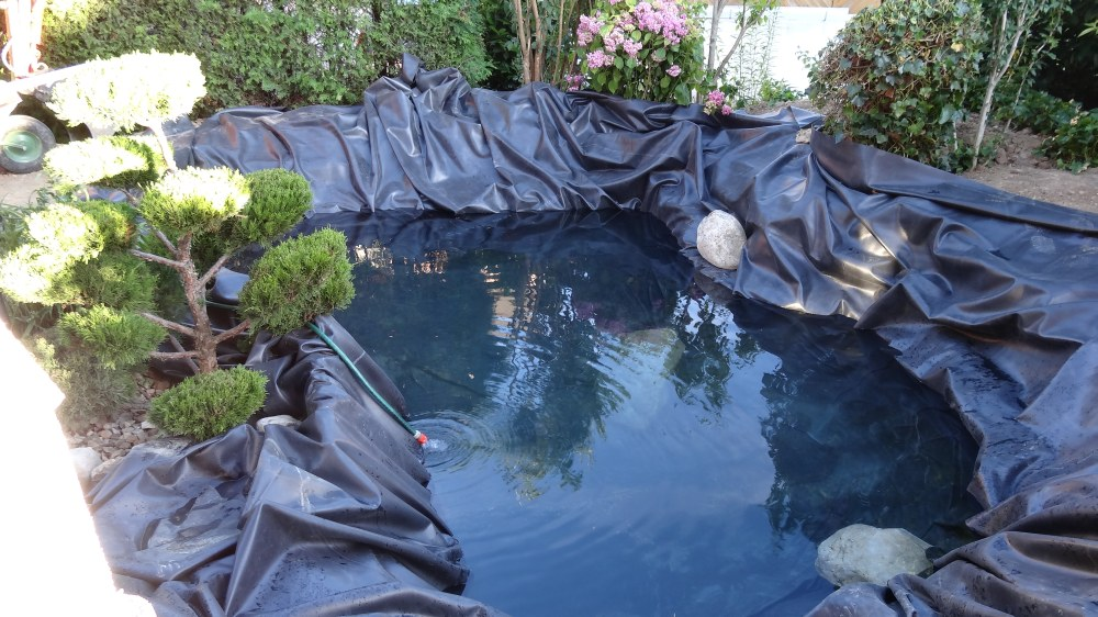 Spezielle Teichfolie ist verlegt und wird erstmals mit Wasser befüllt und die Folie immer wieder ausgerichtet