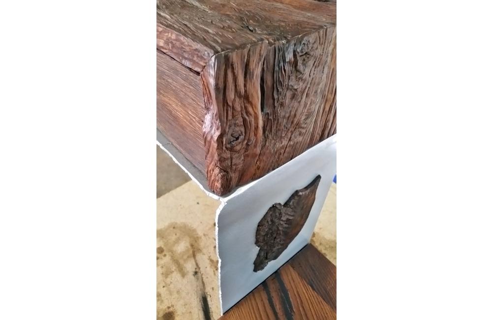 Das Holzstück im senkrechten Blech ist eingelassen. D.h. dass das Eisen ausgeschnitten und das Holz durchgehend ist. Eine Handwerkliche Herausforderung welche gemeistert wurde